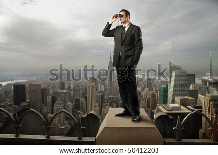 Businessman standing on the top of a skyscraper and using a pair of binoculars