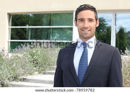 Businessman standing outside a modern house