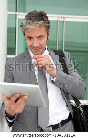 Businessman standing outside building with electronic tablet