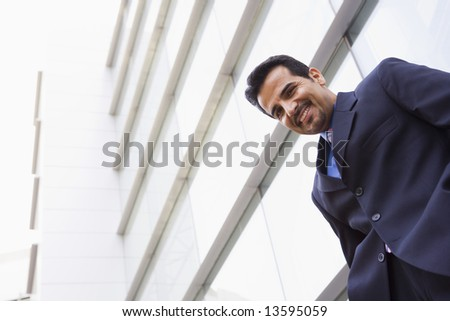 Businessman standing outside modern office building