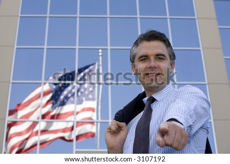 Businessman standing outside the office building with the American flag reflection in the windows