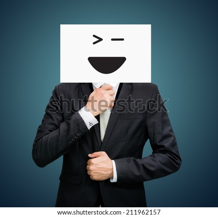 Businessman standing white paper happy smile face holding front of head on dark background
