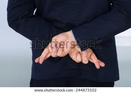 Businessman Standing With Crossed Finger Behind His Back