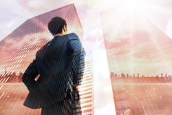 Businessman standing with hands on hips against low angle view of skyscrapers