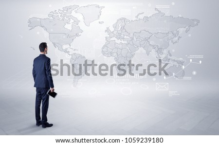 Businessman standing with his back and looking at a worldwide map with objects in his hand #1059239180