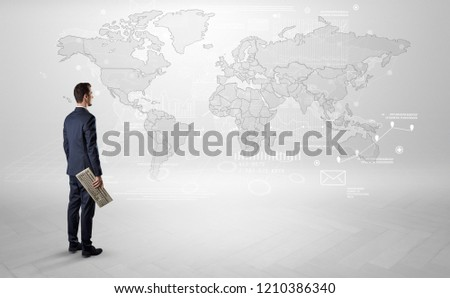 Businessman standing with his back and looking at a worldwide map with objects in his hand #1210386340