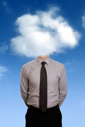 Businessman standing with his head in the clouds concept for daydreaming, contemplation, aspirations or creativity