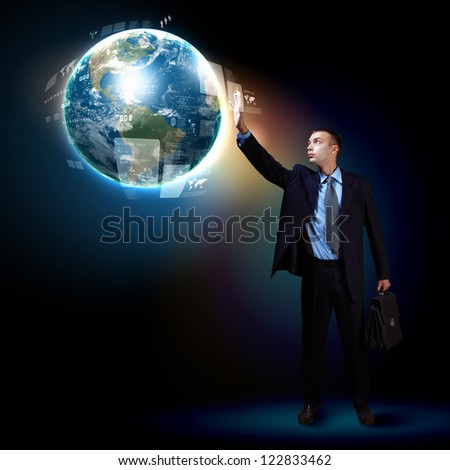 Businessman standing with modern technology symbols next to him. Elements of this image are furnished by NASA