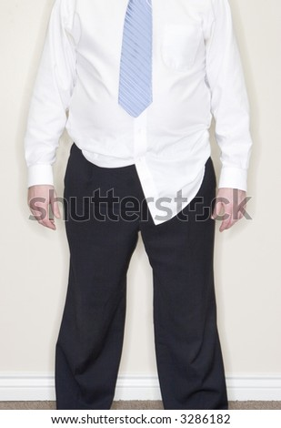 Businessman standing with part of his shirt untucked in his office