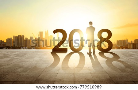 Businessman standing with sunset cityscape background. Ambitions, happy new year 2018 concept. #779510989