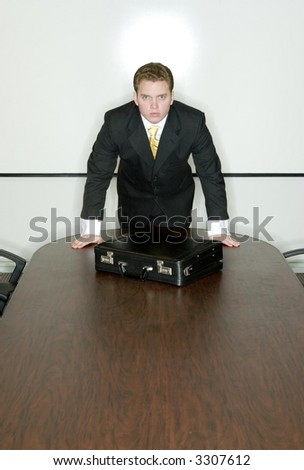 Businessman stands at the head of the conference table with his briefcase in front of him