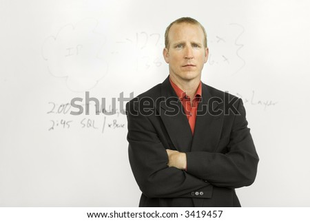 Businessman stands in front of writing board