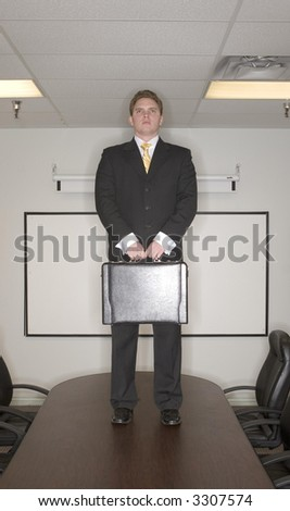 Businessman stands on top of a conference table in the boardroom in success