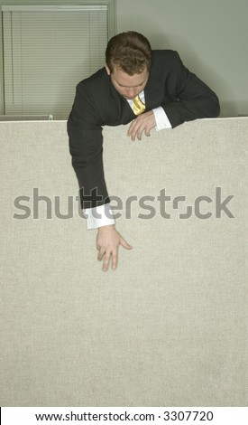 Businessman stands over his cubicle and reaches down to the ground in the office