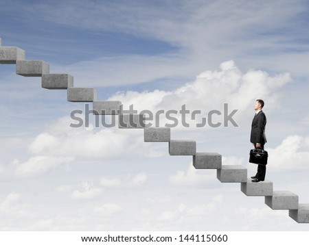 Businessman stepping up a staircase and sky