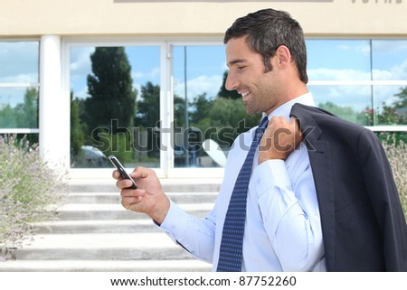 Businessman stood outdoors sending text message from telephone