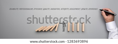 Businessman stopping falling dominos over grey background and male hand writing words reliability, professionalism, efficiency, qua
