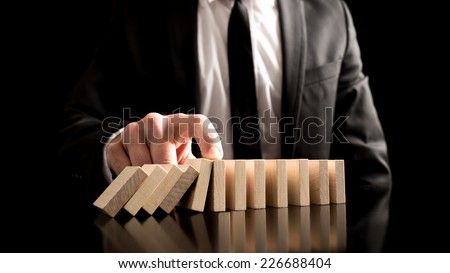 Businessman Stopping the Domino Effect from Small Wooden Blocks on the Table. A Creative Concept for Solution to Problem.