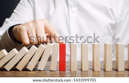 Businessman stops domino falling. Risk management concept. Successful strong business and problem solving. Reliable leader. Stop the destructive processes. Strategy development. Debt restructuring #1433999705