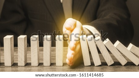Businessman stops domino falling. Strategy development. Debt restructuring. Risk management concept. Successful strong business and problem solving. Reliable leader. Stop the destructive processes.
