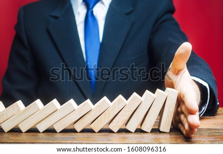 Businessman stops domino falling with his palm. Risk management concept. Successful strong business and problem solving. Stop the destructive processes. Strategy development. Debt restructuring