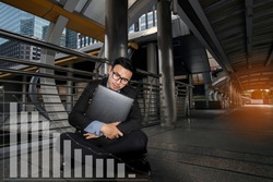 Businessman stress business failure sitting on sidewalk with graph show down shaped. Second wave of COVID-19 crises lead to business failure must be closed, causing unemployment people, layoff.