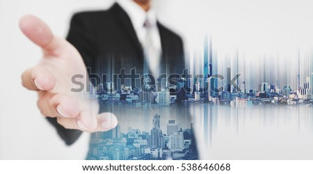 Businessman stretch out hand, with double exposure city and real estate site construction, and hologram futuristic city #538646068