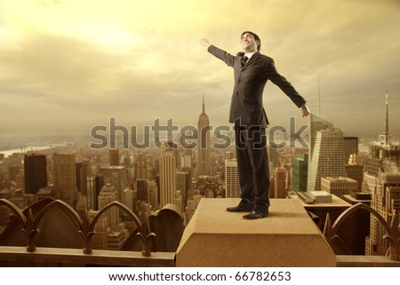 Businessman stretching out on the rooftop of a skyscraper over a city
