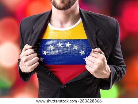 Businessman stretching suit with Venezuela flag on bokeh background