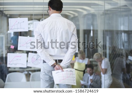 Businessman Studying Documents Stuck To Glass Office Wall