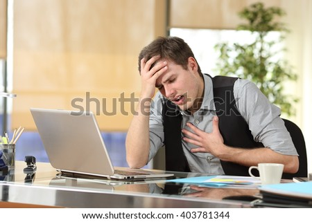 Businessman suffering an anxiety attack with the hands in his chest and head sitting in a desktop at office Stock photo ©