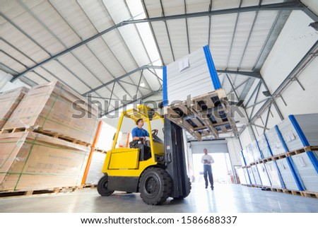 Businessman supervising forklift truck driver worker in solar panel factory warehouse