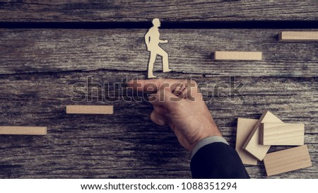 Businessman supporting paper cut out of a man climbing stairs, toned retro effect.