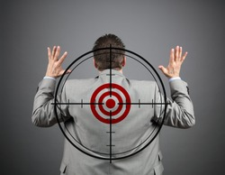 Businessman surrendering with crosshair and target on his back