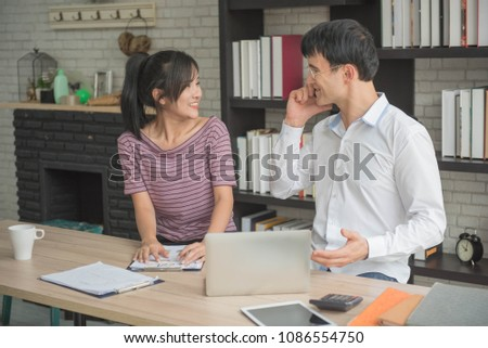 businessman takeing phone and  discuss with businesswoman information  on homeoffice #1086554750