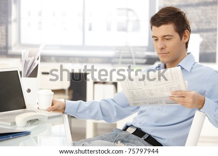 Businessman taking break in office, reading newspaper, having coffee, putting phone aside.?