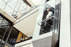 Businessman taking modern glass elevator to the upper floors