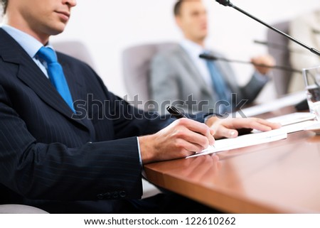 businessman taking notes, meeting businessmen at the table there are microphones and decomposition of business documents - stock photo