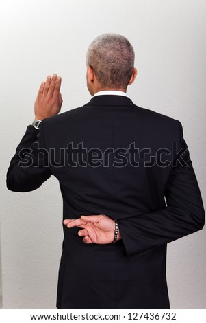 Businessman Taking Oath With Crossed Fingers. Dishonesty concept - stock photo