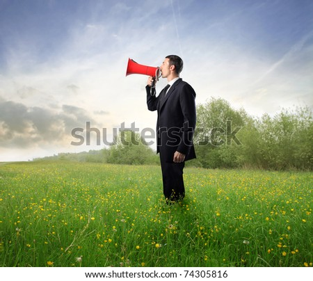 Businessman talking in a megaphone on a green meadow