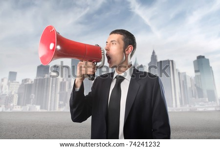 Businessman talking in a megaphone with cityscape on the background