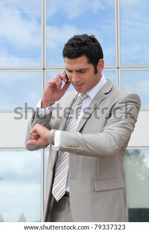 Businessman talking on a cell and checking his watch