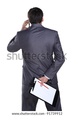Businessman talking on a cell phone holding his files and pencile in other hand