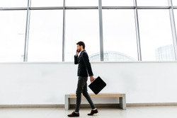 Businessman talking on phone holding a briefcase walking through the office window background