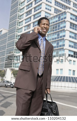 Businessman talking on phone with buildings in background