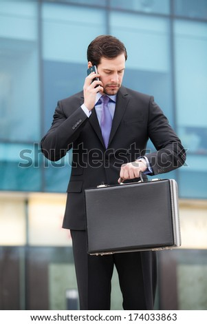businessman talking on the phone in front of an office building with a briefcase in hand and looking at watch