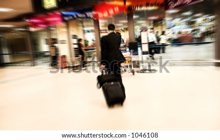 Businessman talking on the phone while rushing to immigration at the airport. Intentional Zoom-effect motion blur.