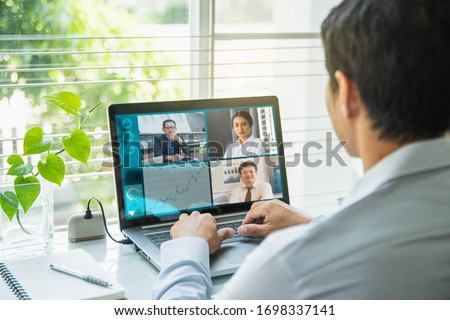 Businessman talking to his colleagues about plan in video conference. Multiethnic business team using laptop for a online meeting in video call.
