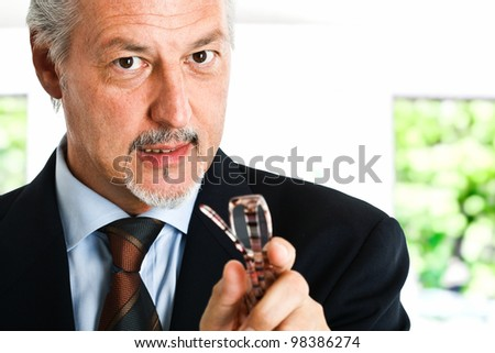 Businessman talking to you while holding his eyeglasses