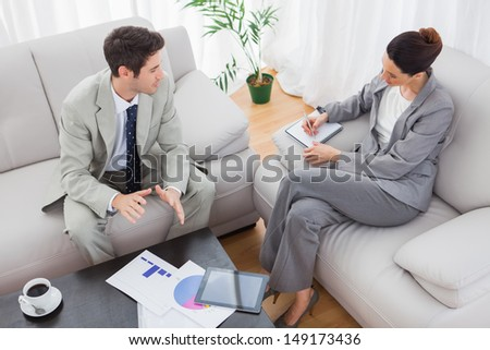 Businessman talking while colleague is taking notes sitting on sofa at office